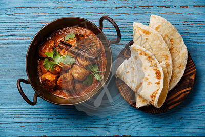 Chicken tikka masala spicy curry meat food with rice and naan bread on blue wooden background