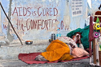 Woman sleeping next to graffiti reading Aids is Cured, Pushkar, Rajasthan, India