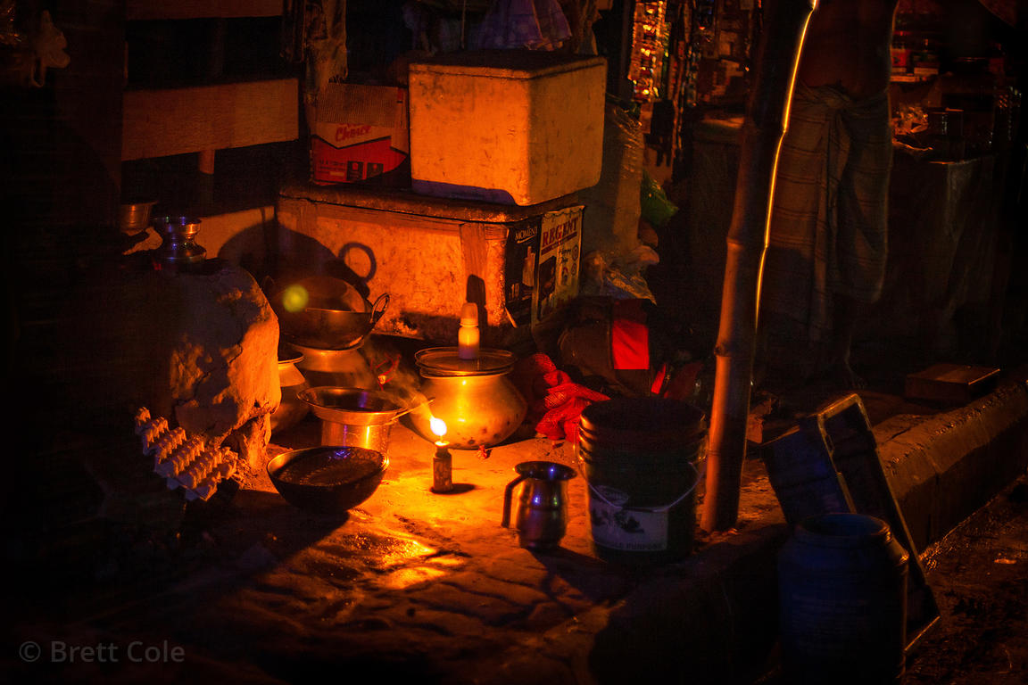 A market stall illuminated by lantern light, near the Lake Gardens Railway Station, Kolkata, India.