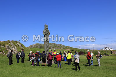 Group of worshippers listening to a Bible reading by St Martin's Cross, Iona Abbey, Iona, Inner Hebrides, Scotland