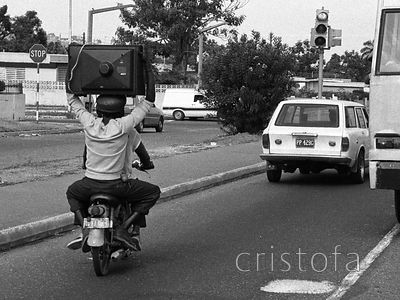 Moped pillion rider carries TV on his head in Kingston