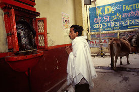 Man prays at a street shrine, Varanasi, India