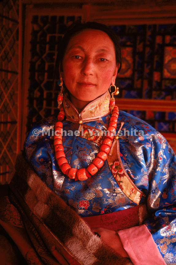 A portrait of a woman from Xiahe wearing an adorned silk dress with a heavy necklace of coral