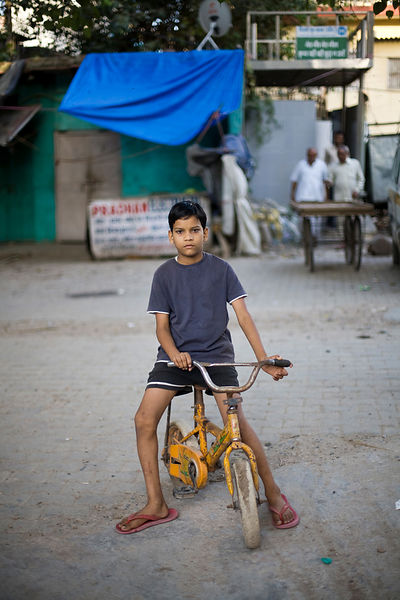 India - New Delhi - A boy on his bicycle near the Chiragh-i-Delhi Dargah
