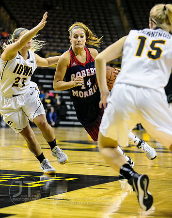Robert Morris' Ashley Ravelli (14) drives between Iowa's Melissa Dixon (21) and Whitney Jennings (15) during the first half o...