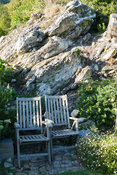 Wooden chairs set against rock outcrop surrounded by rosemary, sedums and wall daisy, Erigeron karvinskianus. The Shute, nr V...