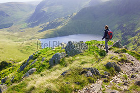 A female hiker walking down Long Stile towards Rough Crag with Blea Water in the distance in the Lake District.