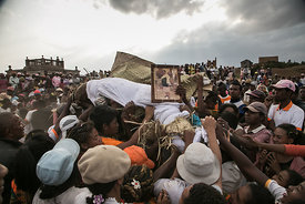 People dance and sing as they carry a body wrapped in a sheet, as they take part in a funerary tradition called the Famadihan...