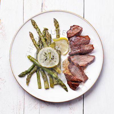 Roast beef with asparagus on white wooden background
