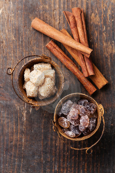 Cinnamon sticks and brown sugar on wooden background