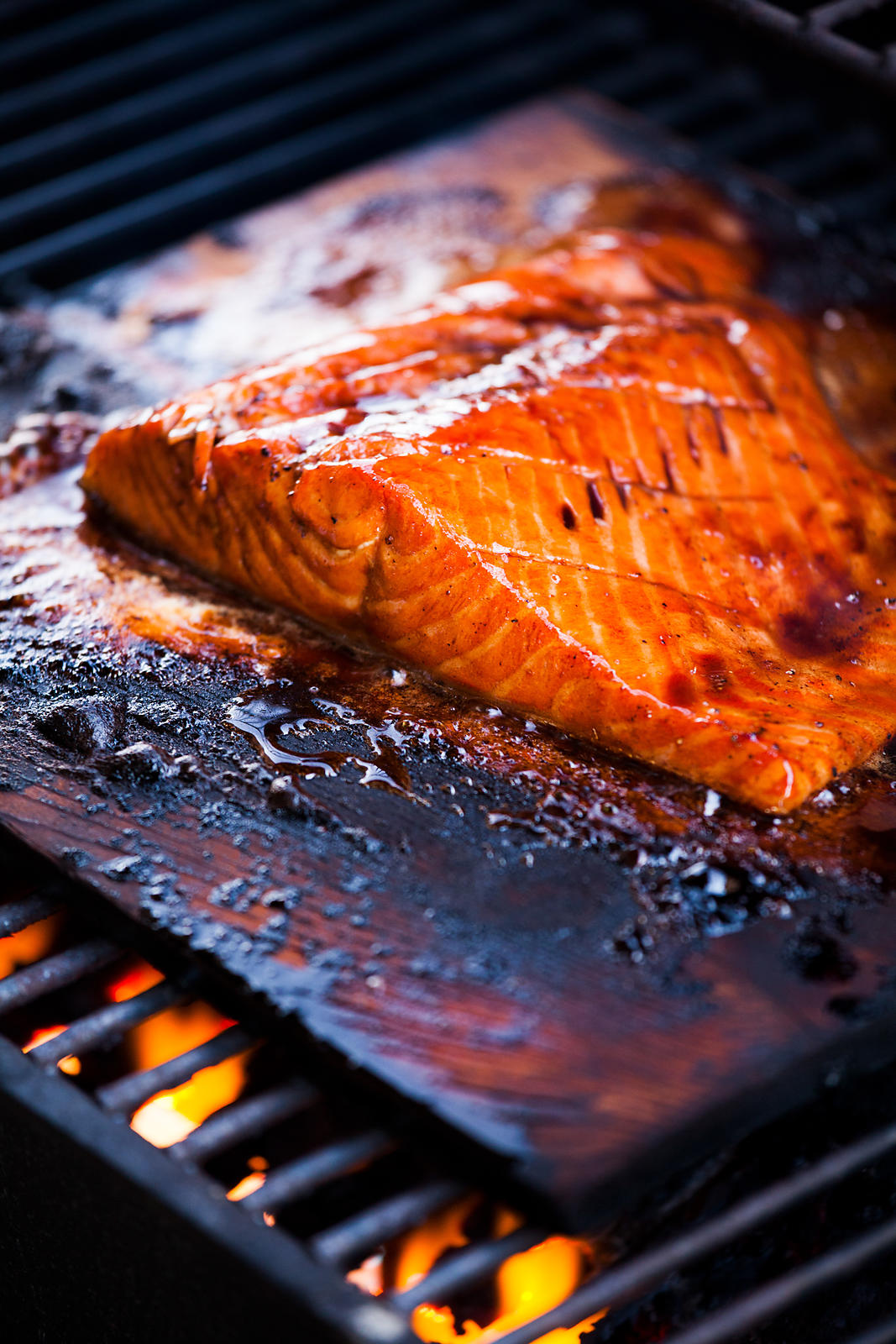 Honey balsamic glazed salmon grilling on cedar wood planks