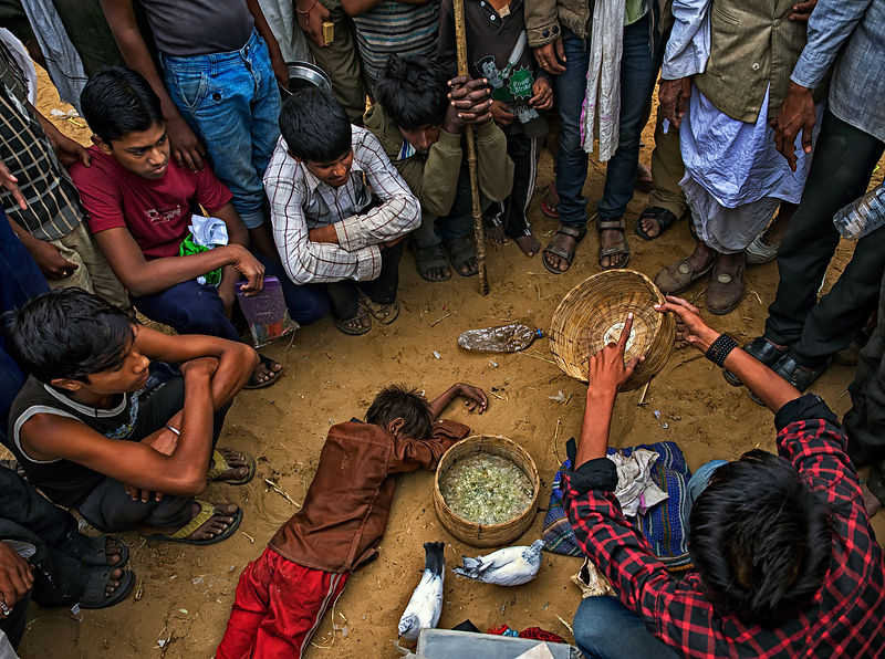 A group of local kids perform a magic trick for the crowd at the back roads of Pushkar, Rajasthan