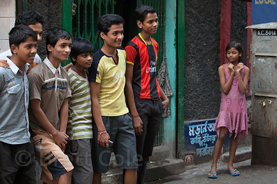 A girl gestures next to a group of boys in Bowbazar, Kolkata, India.