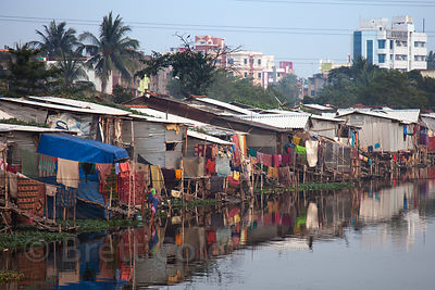 Shanties reflect in a pond called Kalighatpur, Kolkata, India.