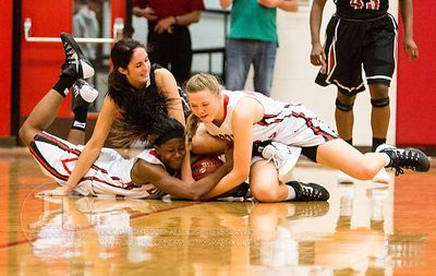 Iowa City High's Kiera Washpu (4) and Courtney Joens (30) wrestle with Waterloo West's Haley Puk (31) for the ball during the...
