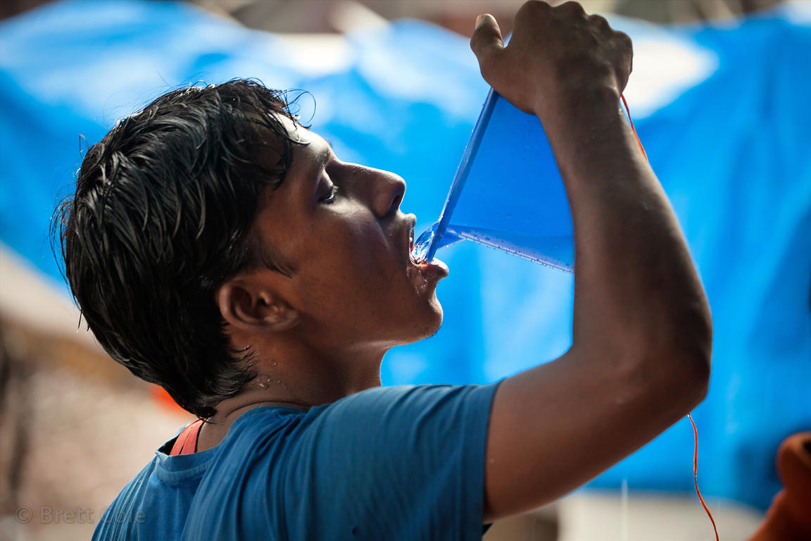 A man drinks water from a public tap at a shop in Crawford Market, Mumbai, India.