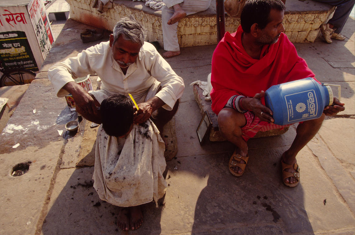 A street barber cuts a childs hair in Varanasi, India