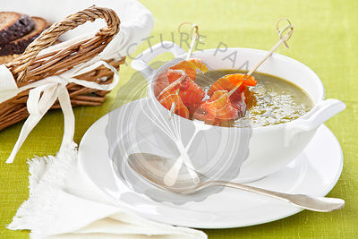 Asparagus soup with smoked salmon on green background