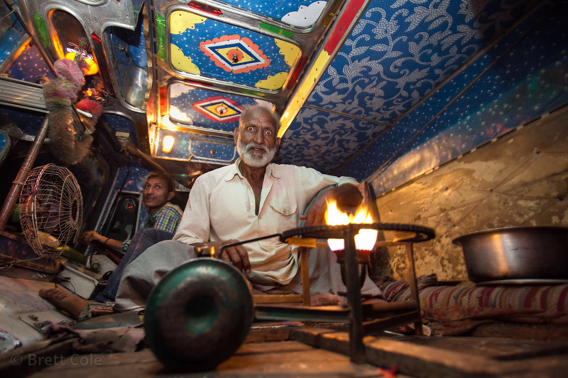 A truck driver cooks dinner in his truck at night, Pushkar, Rajasthan, India