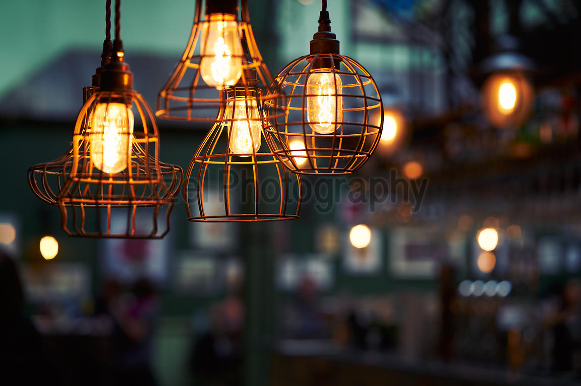 Old rustic lights hanging from the ceiling with a blurred background