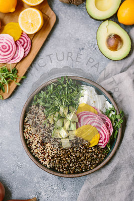 An abundance bowl salad made up of quinoa, sprouts, lentils, avocados, and chioggia beets.