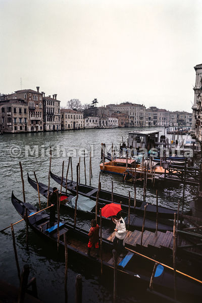 Visitors stay dry with umbrellas on a gondola in the Grand Canal. Venice, Italy, October, 1982.