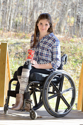 Young woman using a wheelchair relaxing with a coffee on her outdoor deck