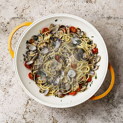 Vongole Shells Clams with tomato and parsley in cooking pan on travertine stone background