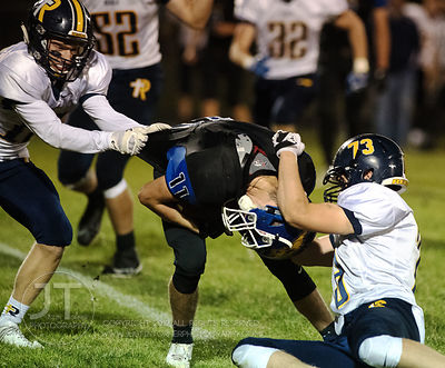 Wilton's Cory Anderson (11) is tackled by Iowa City Regina's Parker Eden (19) and Jack Keller (73) during the second half of ...