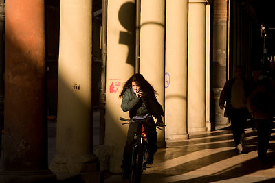 Italy - Bologna - A woman cycles through one of Bologna's many covered arcades