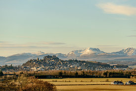 View of the Stirling Castle and the old town in winter with the mountains in the background.