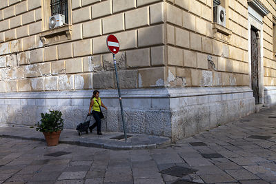 Italy - Palermo - A woman wheels her shopping trolley through the Piazza Bellini