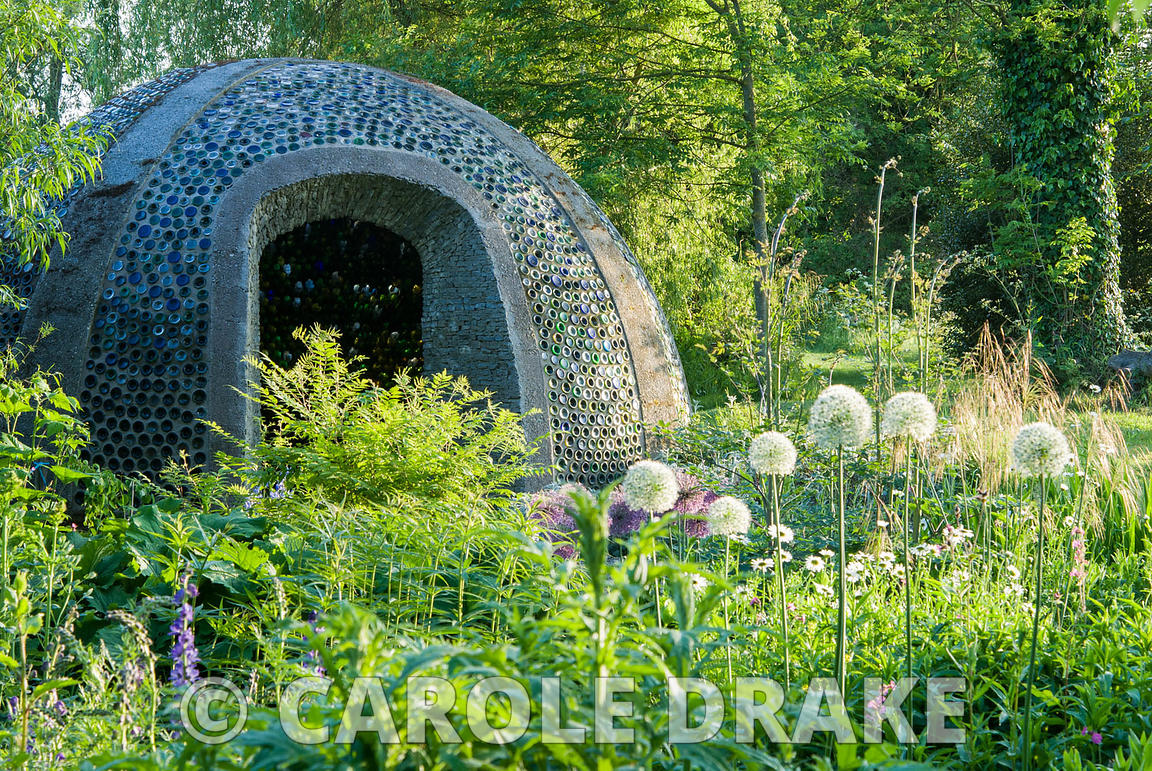 Dome structure constructed using empty bottles, with white Allium stipitatum 'Mount Everest' in foreground. Westonbury Mill W...