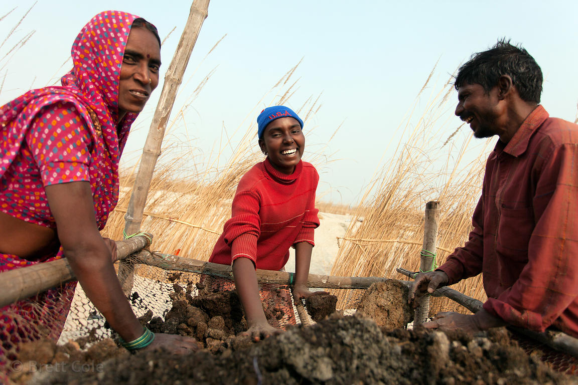 A happy family works sifting dirt in farm fields along the Ganges River near Ramnagar, Varanasi, India.