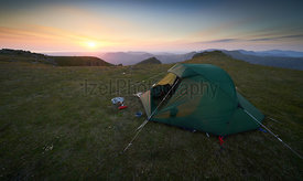 A tent pitched on the summit of Scoat Fell at sunset with views of Ennerdale in. the English Lake District.