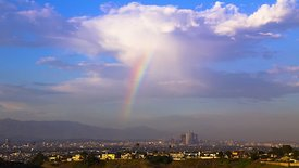 Bird's Eye: Energetic Rainbow Filled Clouds Over Downtown L.A., (Day to Night)