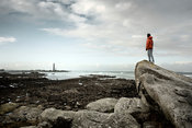 Woman perched on rock observing rocky coast and lighthouse