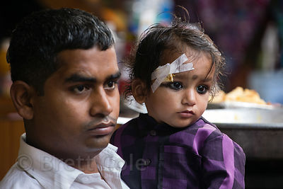 A man and his son, who has a bandaged eye injury, watch a parade Mahashivaratri (Shiva's birthday) in Pushkar, Rajasthan, India