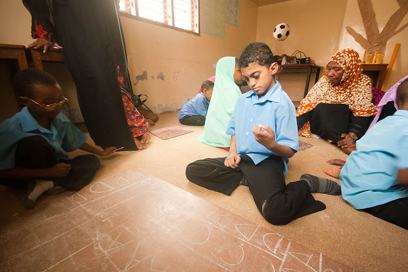 A deaf boy learns his letters on the floor with chalk. The school, run by Zanzibar Outreach Program, first came about as a re...