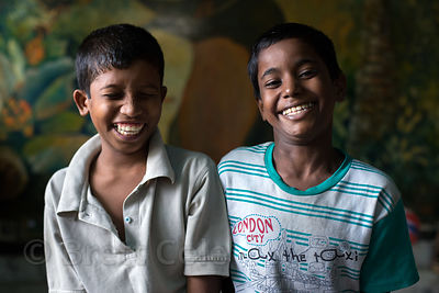 Two friends laugh at a shelter for homeless or otherwise at-risk boys at Sealdah Station, Kolkata, India