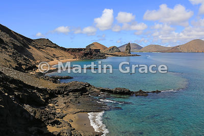 Bartolome Island, with a small submerged volcanic crater in foreground and Pinnacle Rock beyond, looking to Santiago, Galapag...