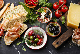 Italian snacks food with Ham, Sliced bread Ciabatta, Olives, Feta cheese with dried tomatoes and Parmesan cheese on dark marb...