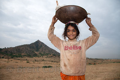 A girl collects camel dung for fire fuel, Pushkar, Rajasthan, India
