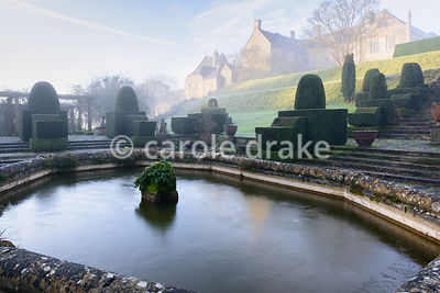 The Fountain Court on a winter's morning at Mapperton, Dorset, featuring clipped yews and decorative urns around a central fo...