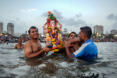Families immerse statues of Ganesh into the Arabian Sea at Chowpatty Beach during the Ganesh Chaturthi Festival, Mumbai, India.