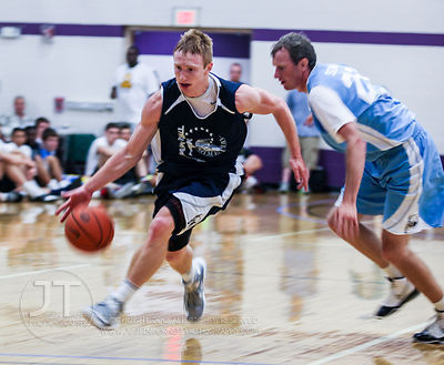 Iowa's Mike Gesell dribbles down the court past ex-Winona St player Kyle Schlaak during Primetime League play at the North Li...