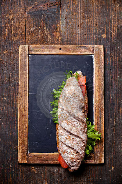 Sandwich with smoked salmon on vintage slate chalk board background