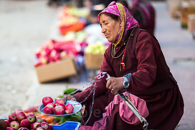 A Ladakhi woman weighs apples at a market in Leh, Ladakh, India