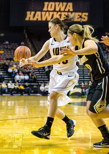 Iowa's Christina Buttenham (23) and Purdue's Hayden Hamby (10) vie for a loose ball during the first half of play at Carver-H...