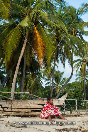 Woman sitting on palm-lined beach, Nosy Be, Madagascar